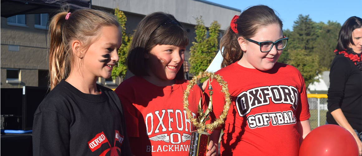 Middle School students posing with trophy from tailgate competition
