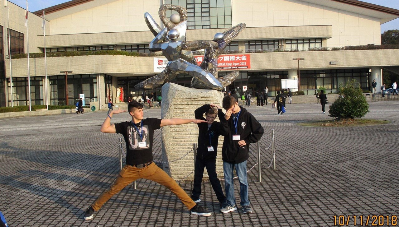picture of three boys in Japan in front of statue at RoboRave