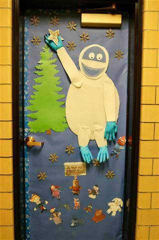 Large abominable snowman putting star on pine tree and picture of mini misfits