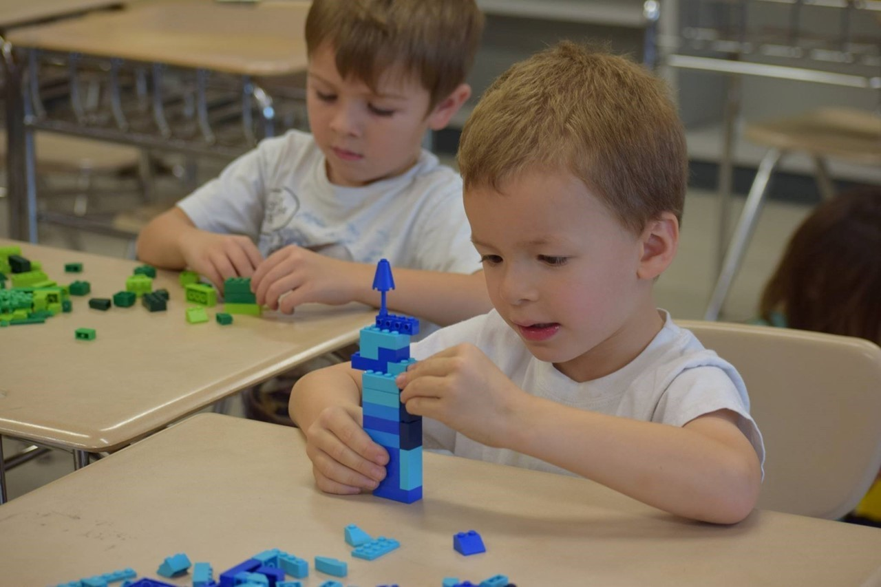 two young boys playing with Legos on school desks