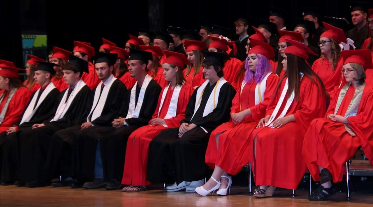 2018 graduates sitting on stage in cap and gown