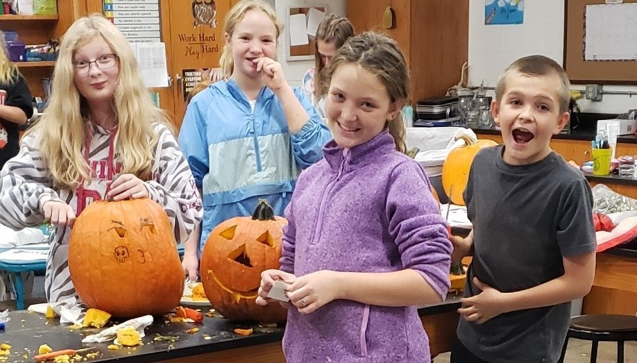 Middle school students carving pumpkins
