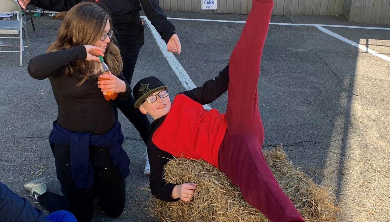 Three middle school students playing on a bail of hay at the Oxtoberfest community event