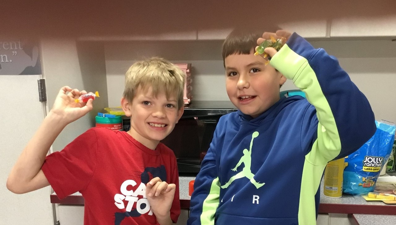 Two boys holding up Jolly Rancher candy that they are going to melt