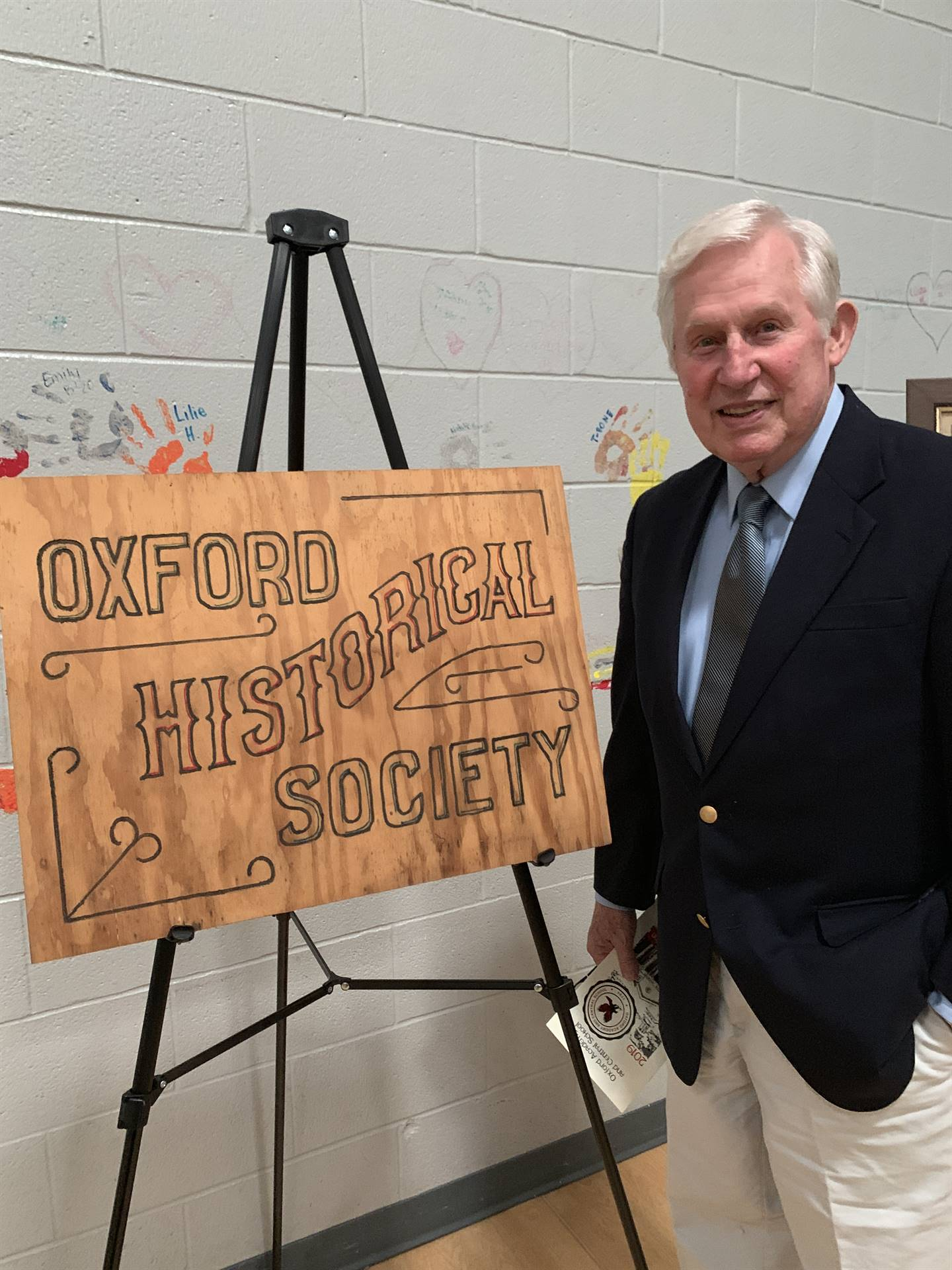 Mr. Lanfear posing with historical society sign display