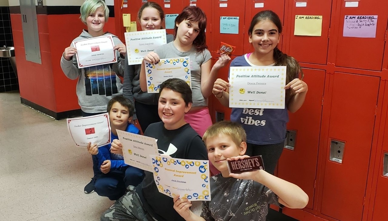 Kids showing their awards and gifts for improving attendance and behavior
