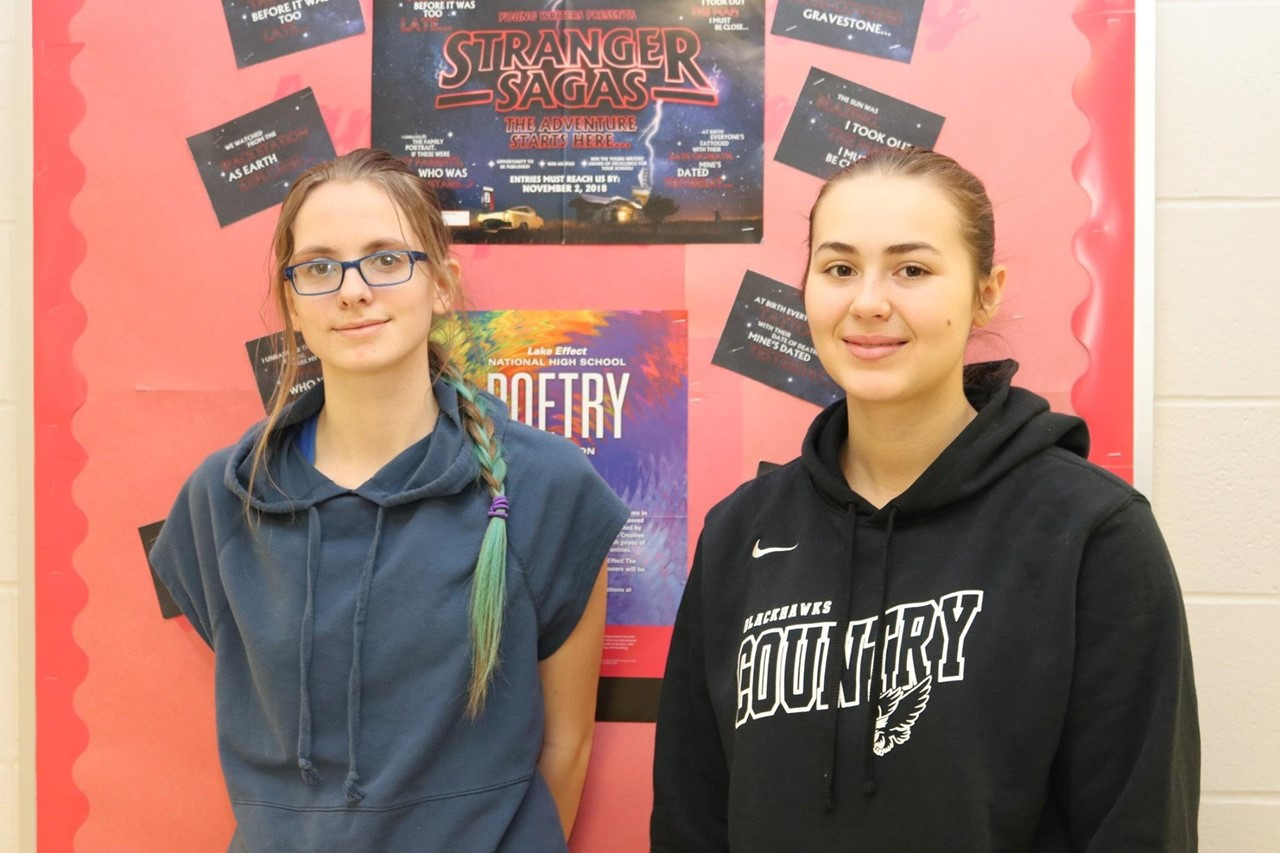two female girls standing in front of a bulletin board of posters