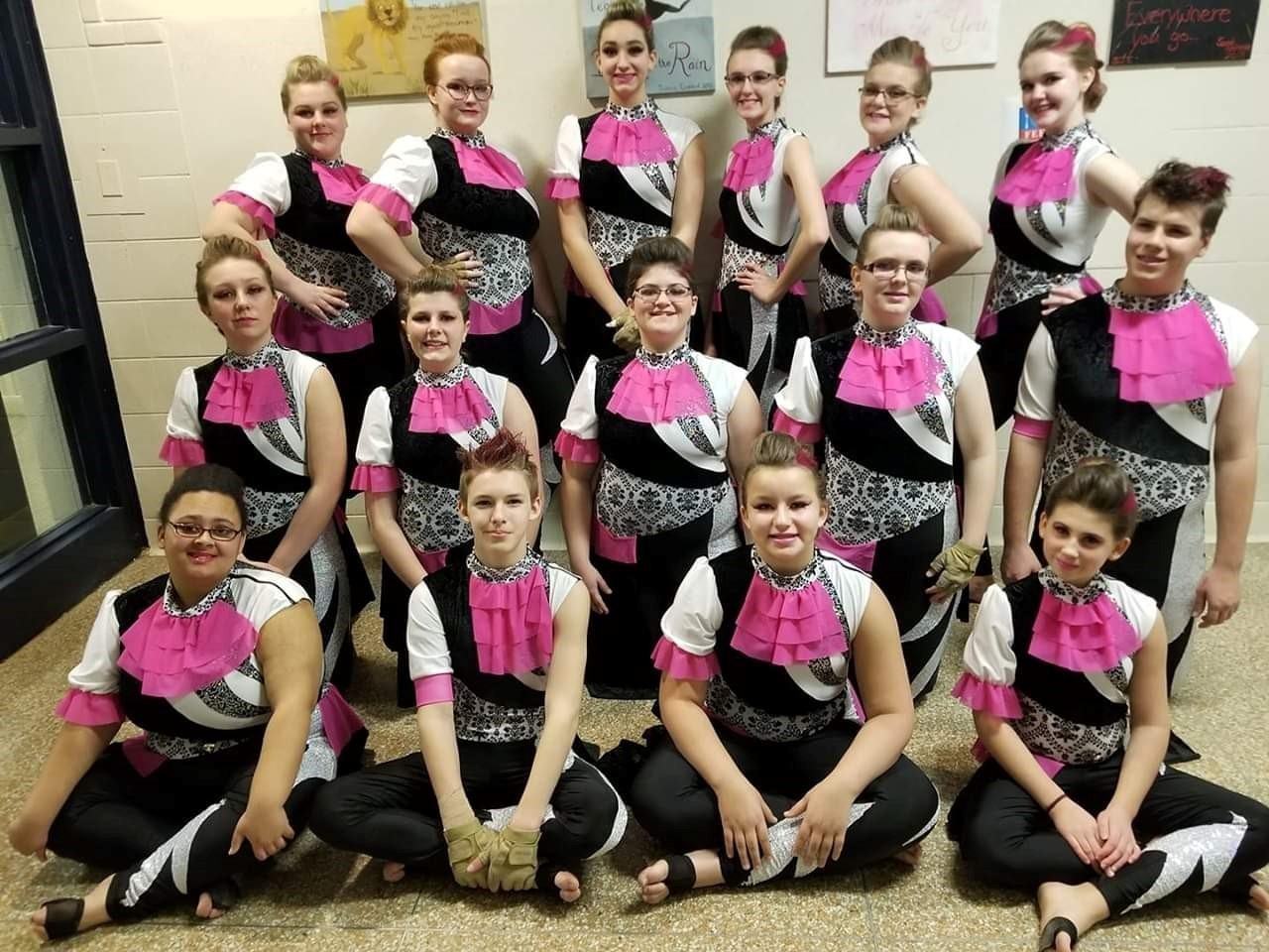 winterguard members posing in their pink, white and black costume from their win