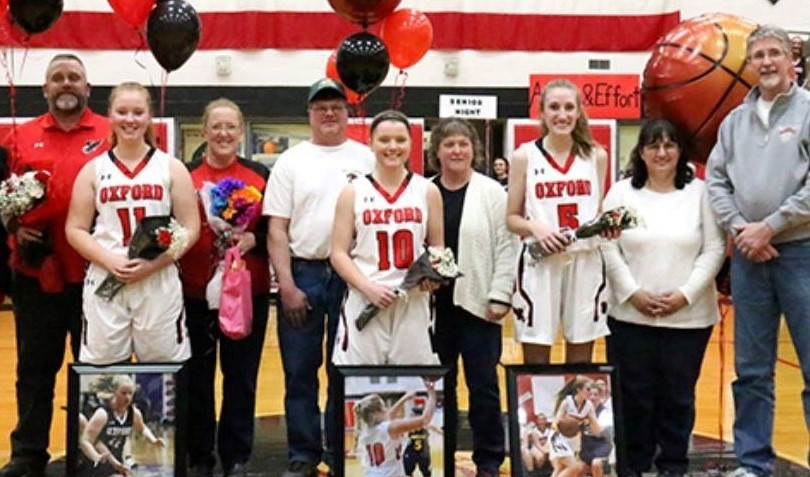 senior varsity girls basketball players posing with their parents