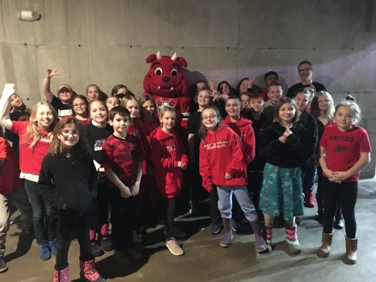 4th grade students posting with Devils mascott before singing