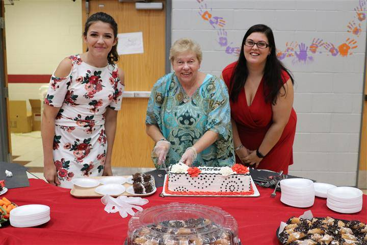 picture of three ladies cutting and serving cake
