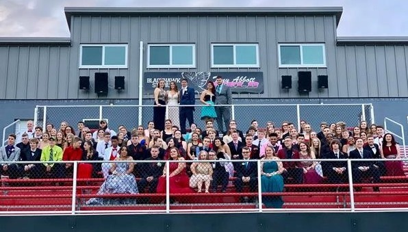 Prom attendees posing on football stadium bleachers