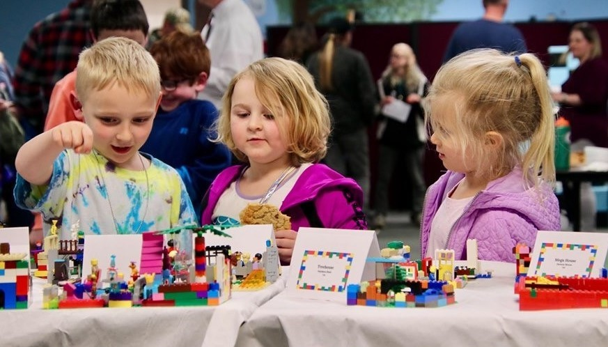 3 primary school students viewing Lego creations