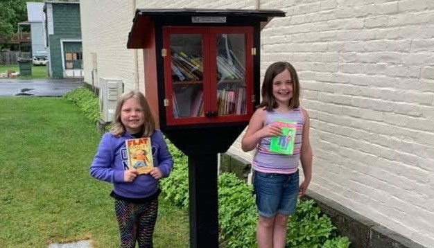 Two students pick books from the free book exchange cabinet in town