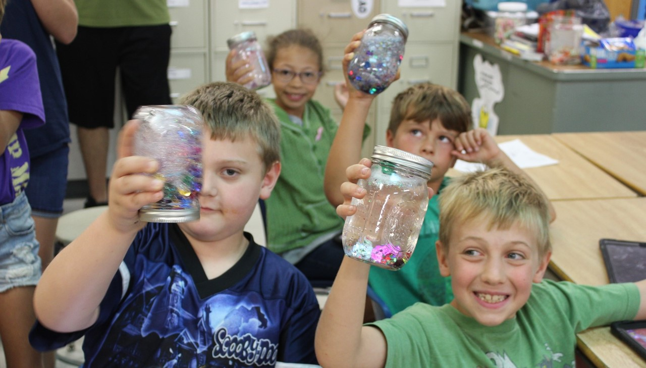 Three boys and a girl shaking the snow globe they created from a mason jar and confetti