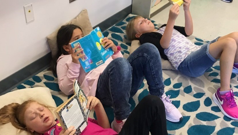 Three students reading books while laying down