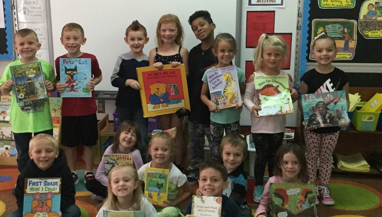Classroom students showing off their books