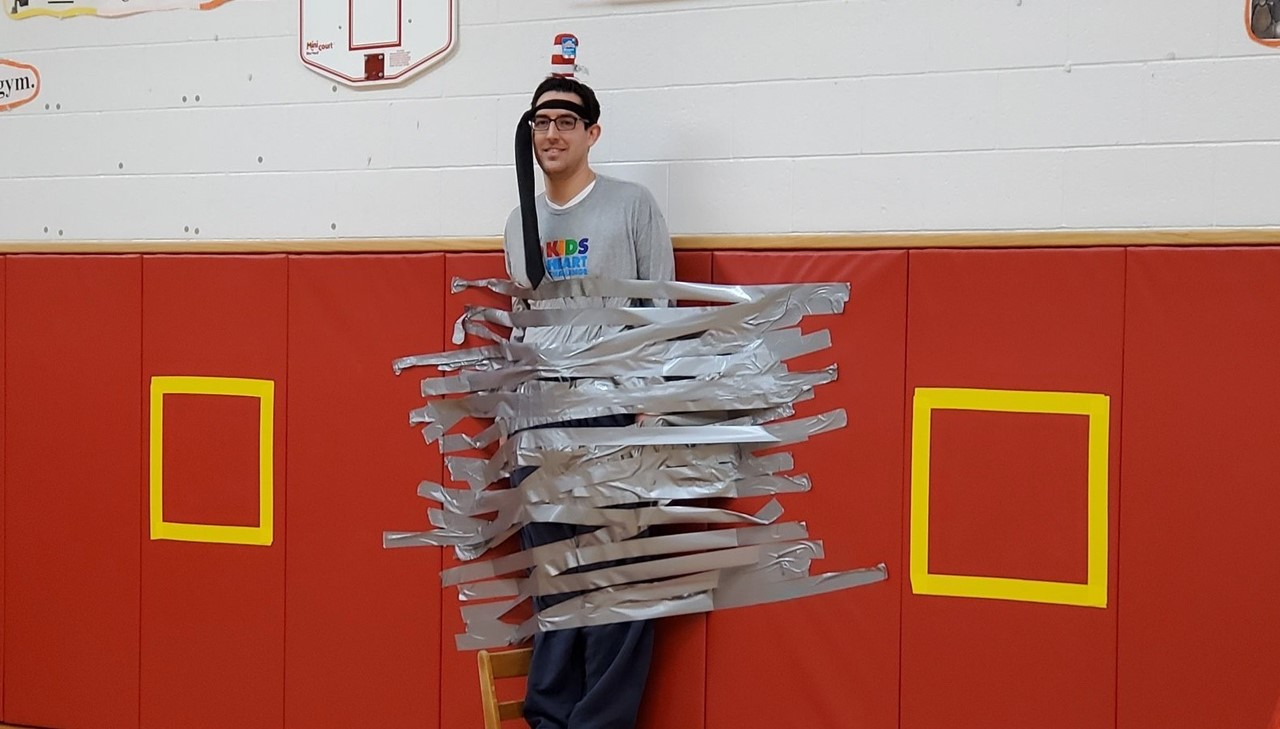 Principal Collier is duct taped to the wall in the gym.