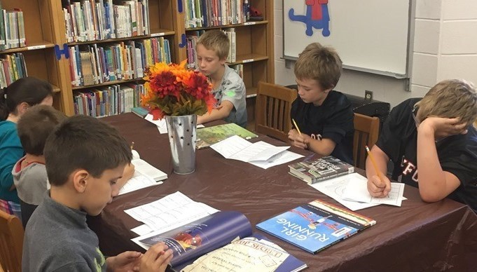 Primary school students reading books at a table in the library.