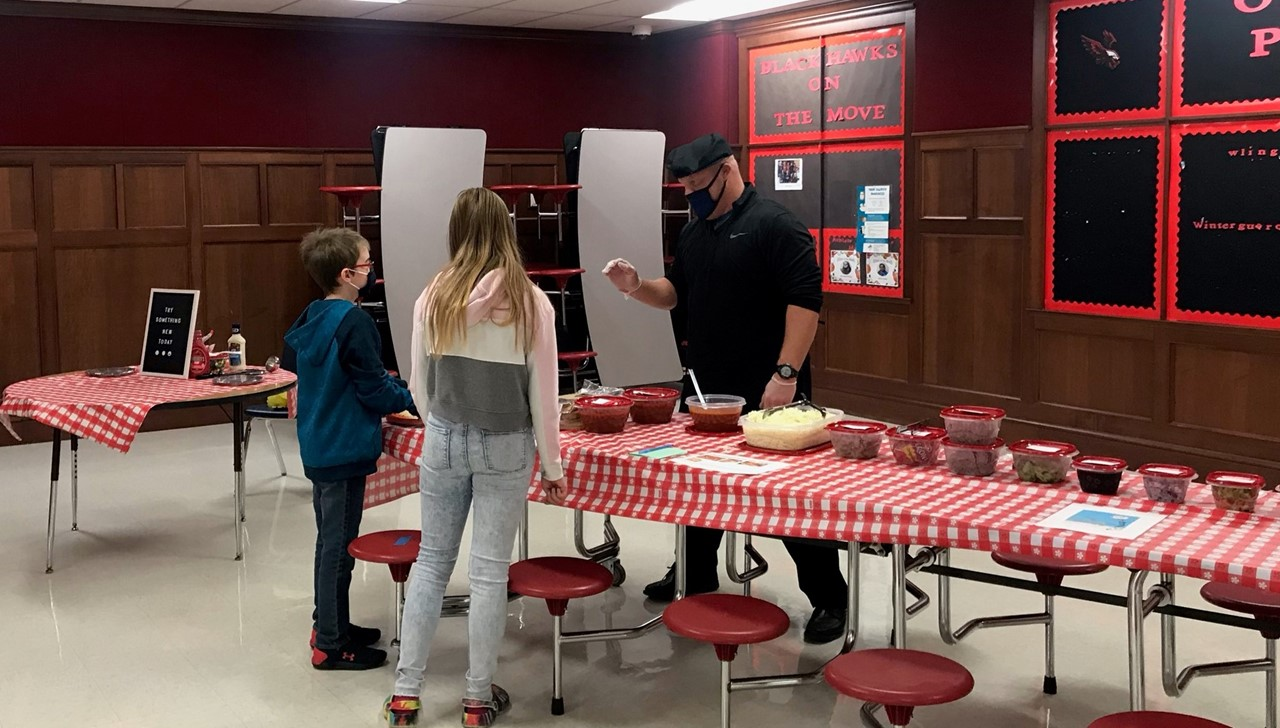 Two middle school kids selecting their pizza making choices