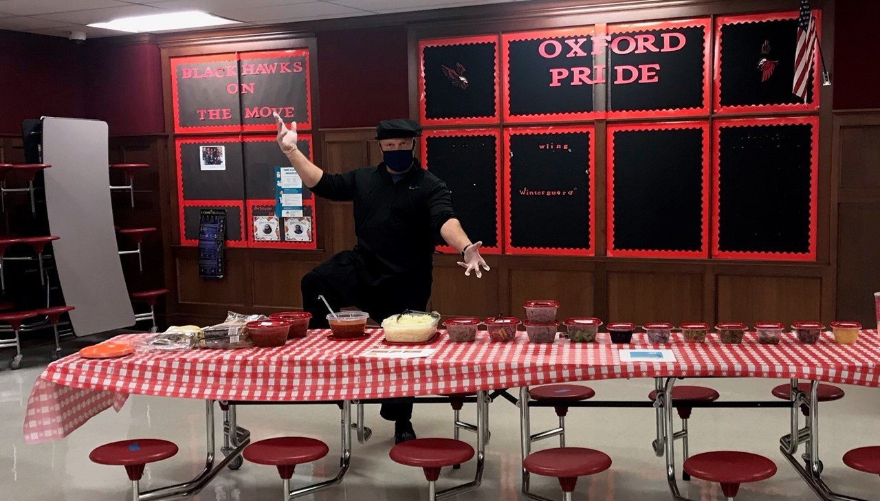 Mr. Holmquist standing in front of pizza making items for students to make their own pizza