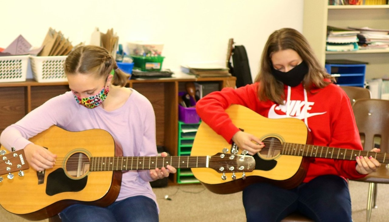 middle school students playing guitar