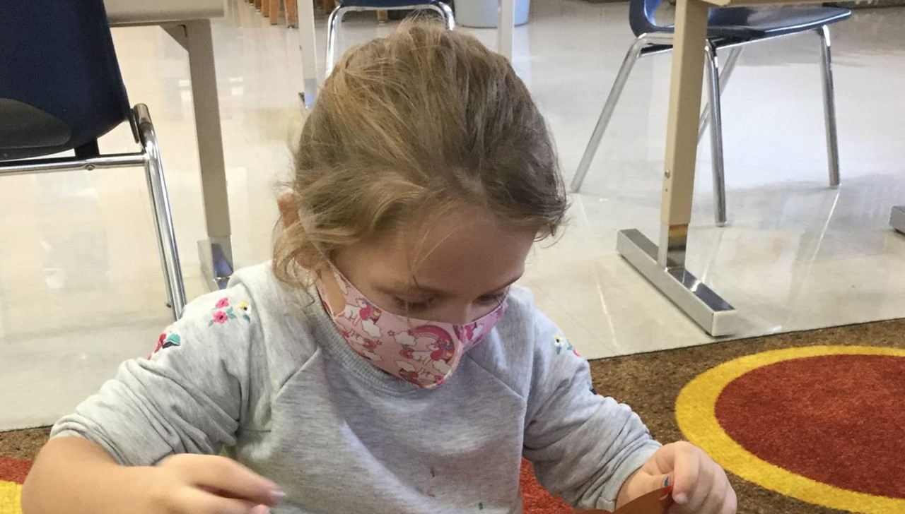 Primary school student sewing a paper apple