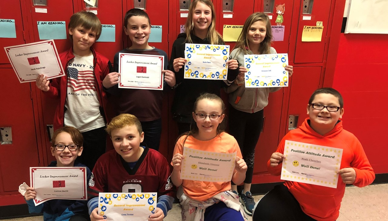 Middle school students posing with their awards