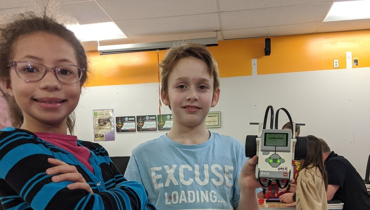 Two students showing their robot they created