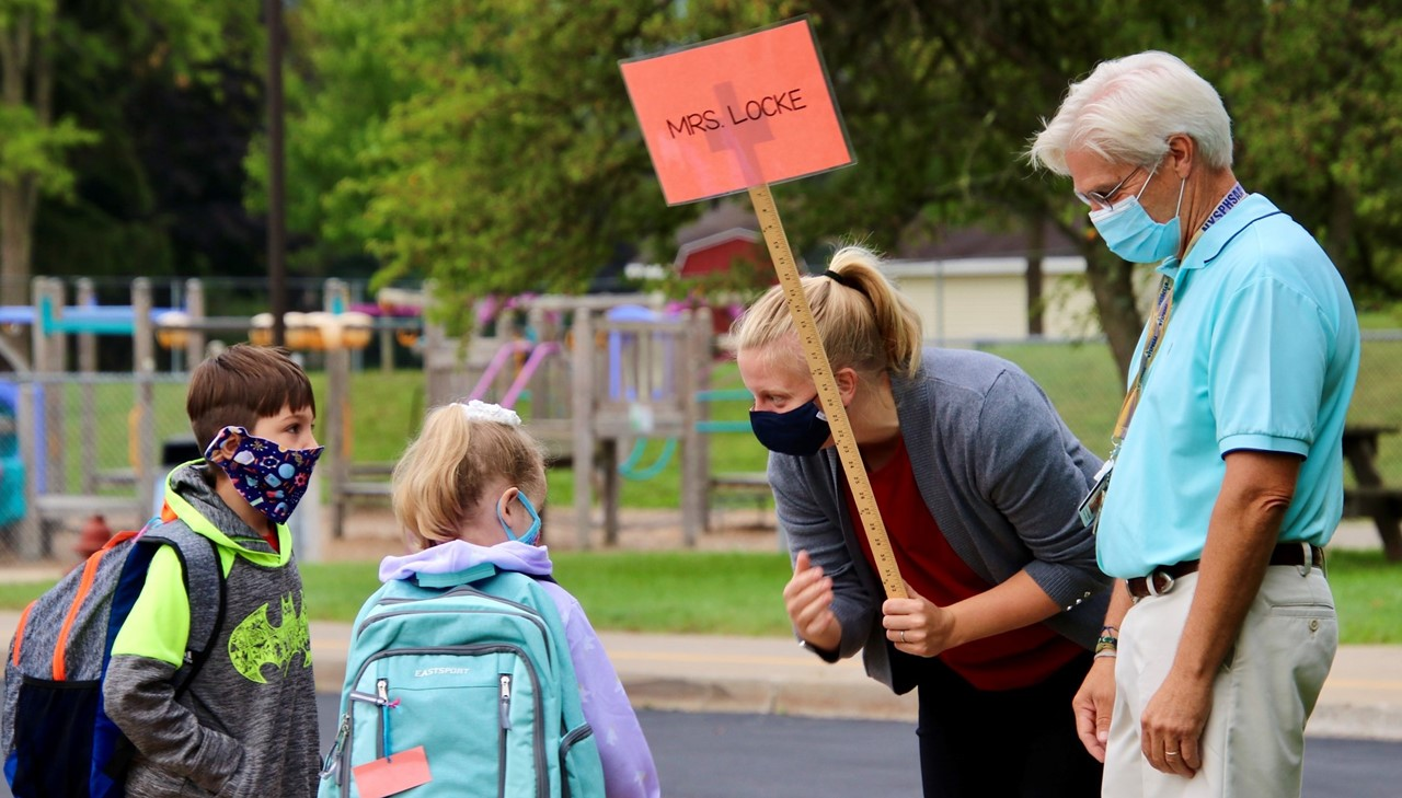 Mrs. Locke welcoming a few of her students back to school