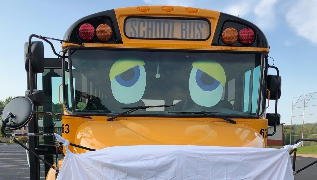 A school bus supports wearing a mask (sheet is drapped across the front)