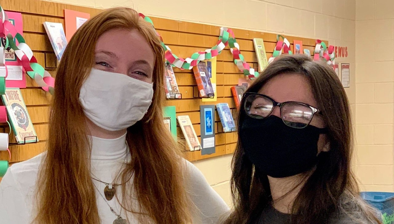 Two high school girls posing with masks