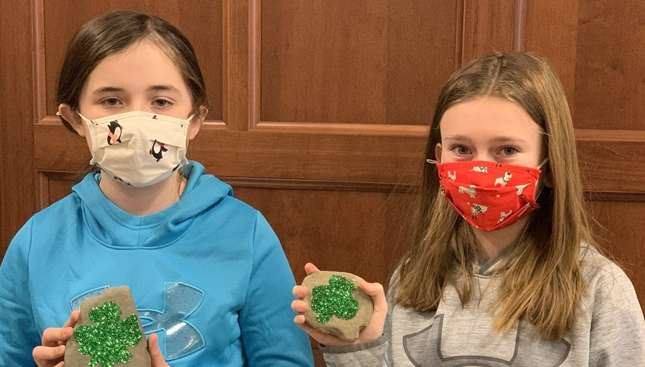 Two middle school girls showing their painted rocks
