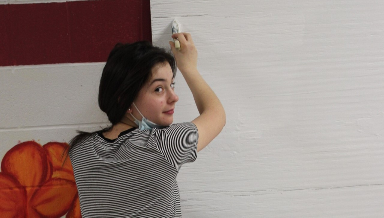 HS female painting a sign
