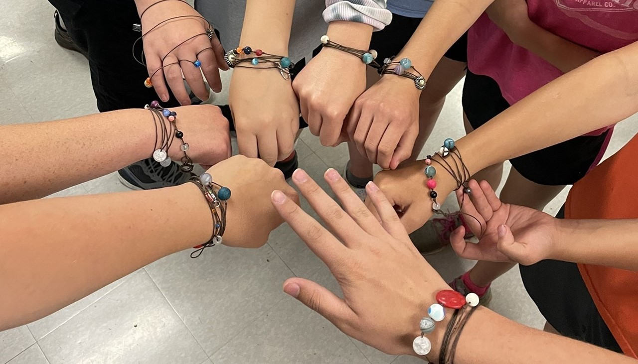 hs steam program kids - displaying the bracelets they made