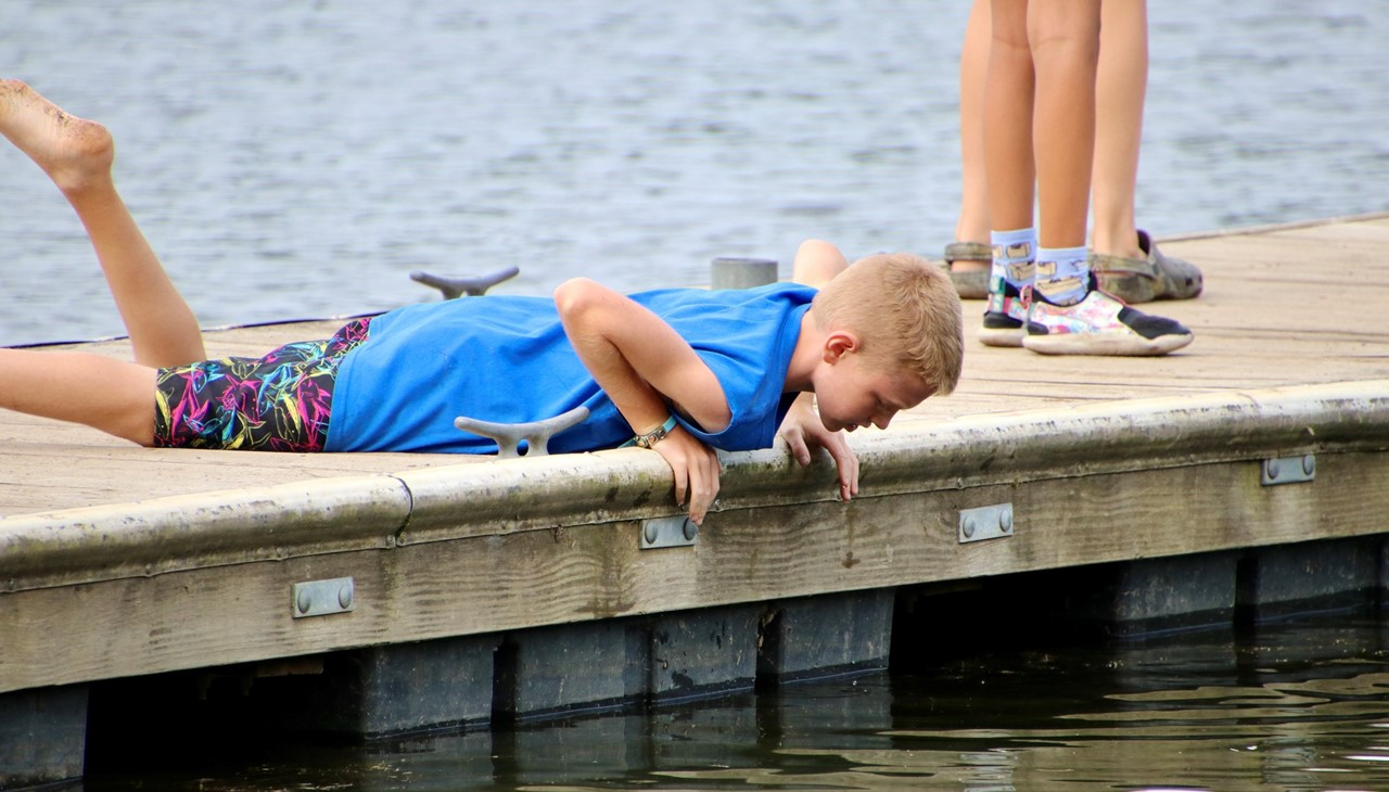 Bowman Lake trip - boy on dock looking into the water