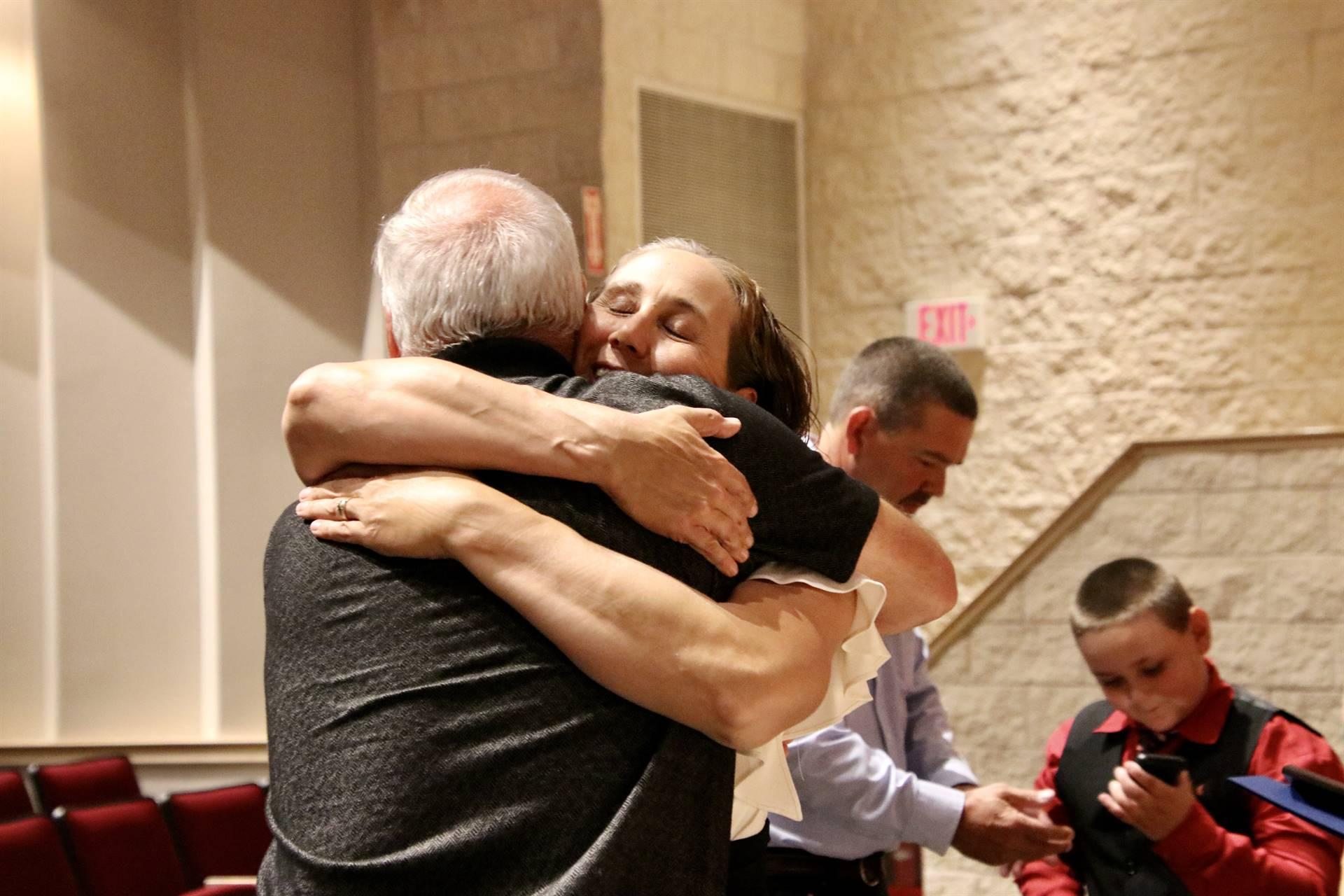 Hall of Distinction honoree Barrows hugging presenter Carey