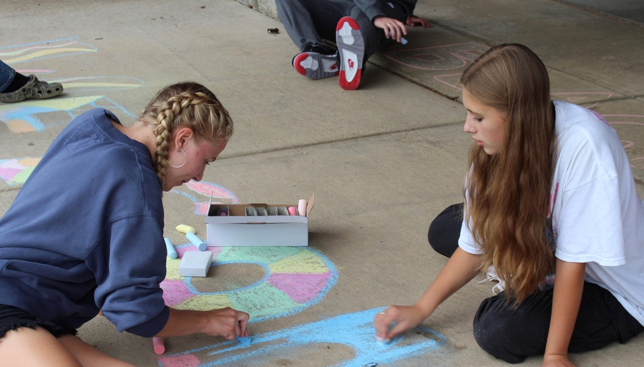 Art students creating welcome back signs with chalk on the sidewalk
